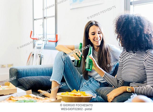 Friends clinking beer bottles sitting on the sofa
