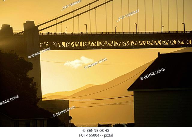 Low angle view of Golden Gate Bridge in city during sunset, San Francisco, California, USA