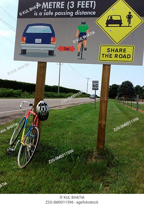 Illustrated share the road sign, Ontario Canada. Recommends space of one meter between cars and cyclists