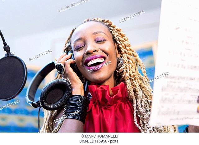 African American singer recording in studio