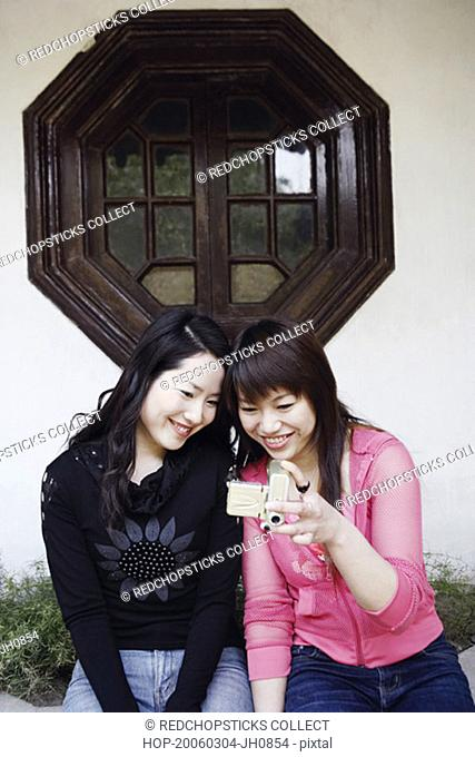 Two young women sitting looking at a digital camera