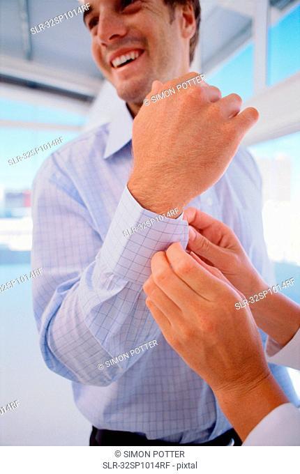 Woman buttoning businessman?s cuffs