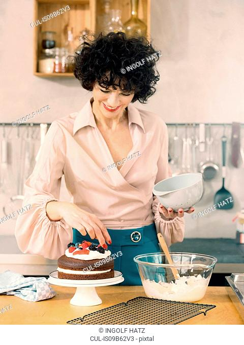 Woman decorating chocolate cake with dairy cream and fresh summer fruits