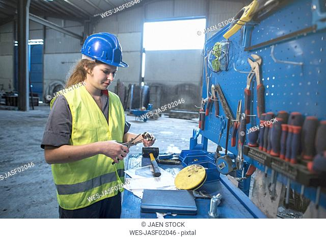 Woman working in factory adusting metal pieces