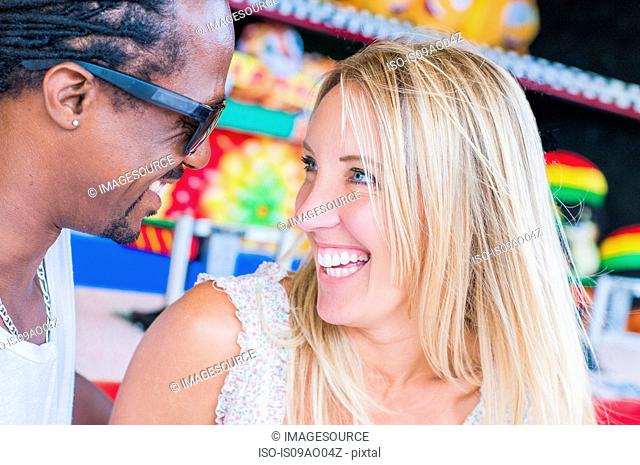 Multi ethnic mature couple laughing at amusement park