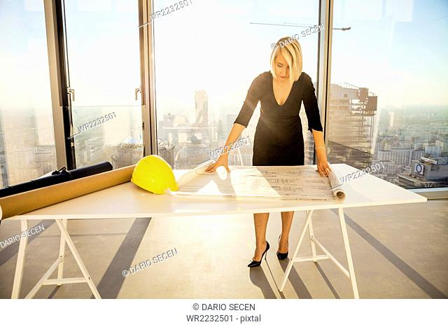 Businesswoman in office examining blueprint