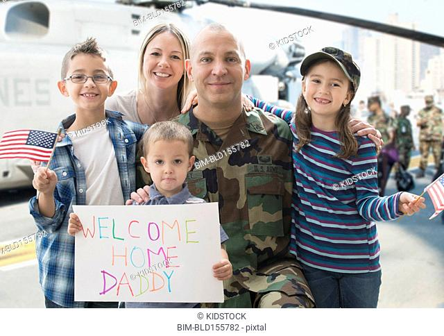 Caucasian returning soldier and family smiling near helicopter