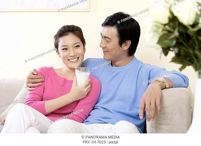 Young man looking at young woman holding glass of milk