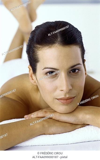 Woman lying on stomach with head resting on arms, portrait