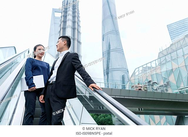 Young businesswoman and man talking while moving up city escalator, Shanghai, China