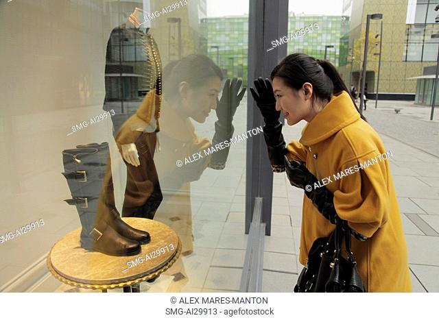 Young woman looking in shop window shopping