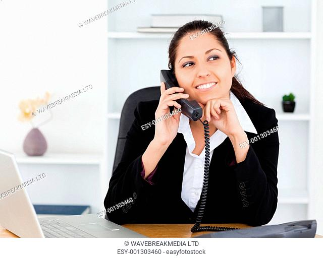 A beautiful smiling businesswoman on the telephone in her office