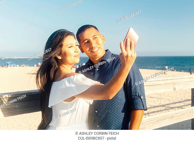 Couple beside beach, talking selfie, using smartphone, Seal Beach, California, USA