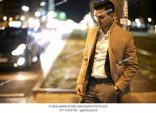 young Afghan man with closed eyes at street at night, next to car traffic, in Berlin, Germany