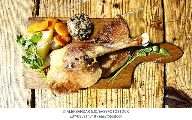 Roasted goose legs and breasts on a wooden table