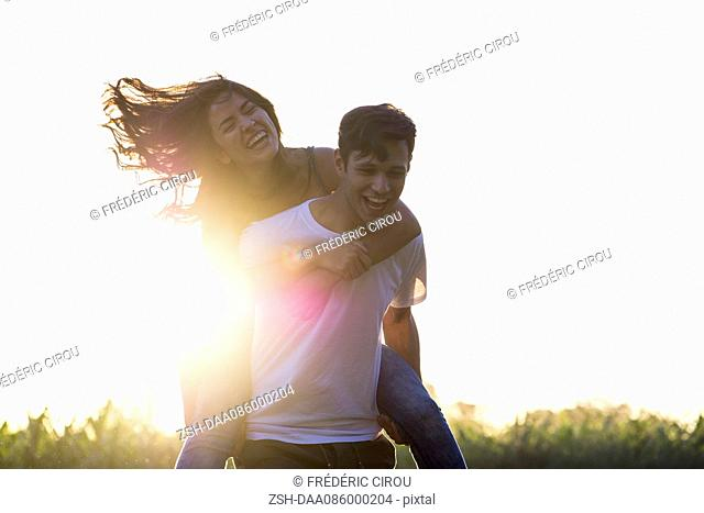 Man giving girlfriend piggyback ride