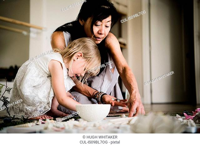Woman and child making arrangement on floor