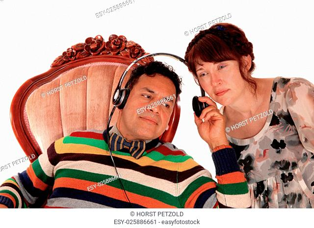 A middle age Hispanic man sitting in a armchair with headphone, listening.to music and his wife listening too, isolated for white background.