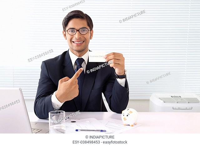 Young professional man showing business card at office with laptop computer and piggy bank on table