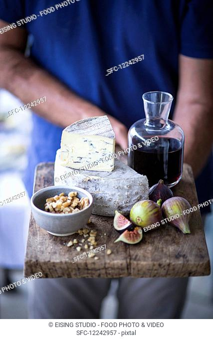 A man holding a cheese board with blue cheese, figs, nuts and wine