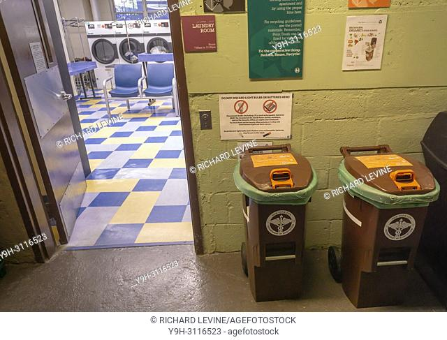 Bins for the New York Dept. of Sanitation Organic Waste Collection program in an apartment building service area in the Chelsea neighborhood of New York on...