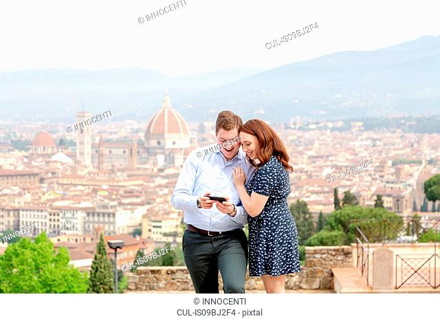 Young couple smiling at mobile phone, Santa Maria del Fiore in background, Florence, Toscana, Italy