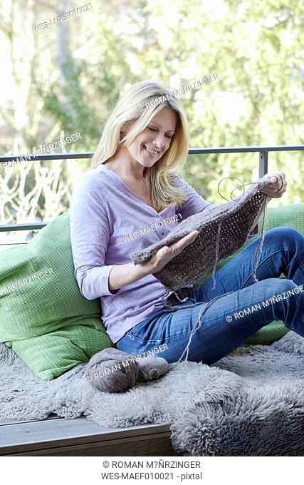 Blond woman sitting on balcony with knitting