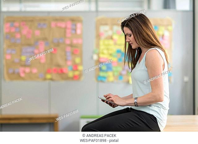 Businesswoman sitting on desk in office using cell phone