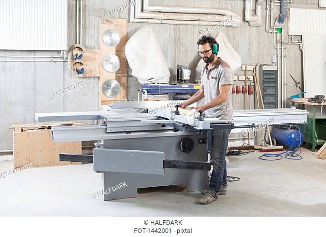 Full length of carpenter using a sliding table saw in workshop