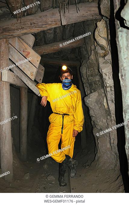Bolivia, Potosi, tourist wearing protective clothing standing in adit of the Cerro Rico silver mine
