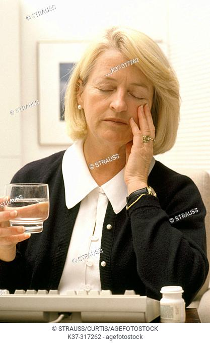 Mature woman with glass of water, suffering from headache