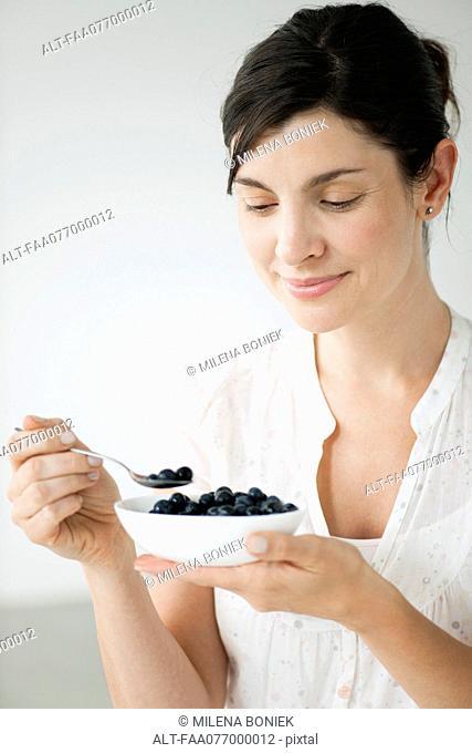 Woman eating bowl of fresh blueberries