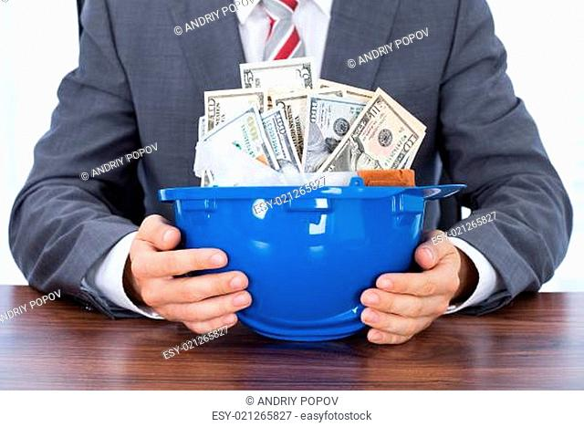 Businessman With Hardhat Full Of Banknotes At Desk