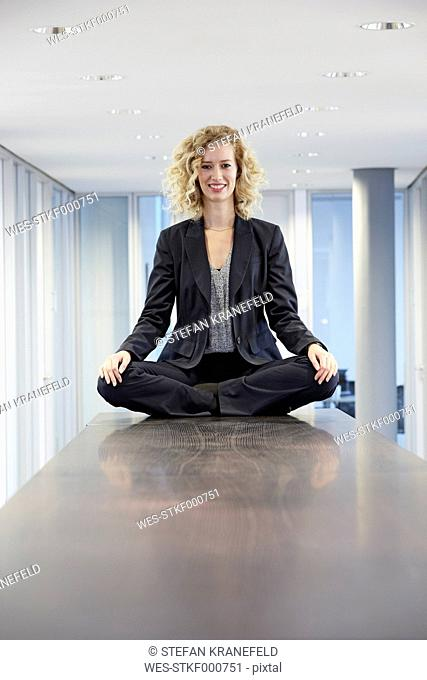 Germany, Neuss, Young business woman sitting cross-legged on table