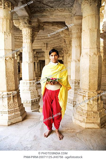 Teenage boy holding religious offering in a temple, Adinath Temple, Jain Temple, Ranakpur, Pali District, Udaipur, Rajasthan, India