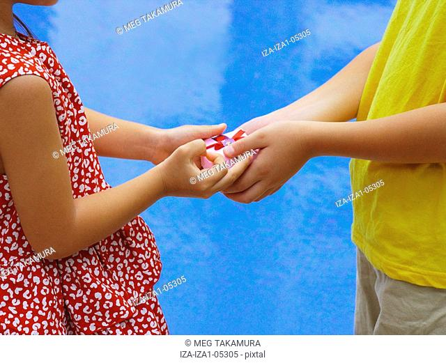 Mid section view of a boy taking a gift from a girl at the poolside