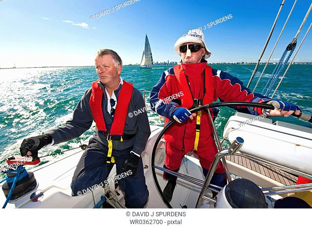 Senior citizen captain steers yacht during race
