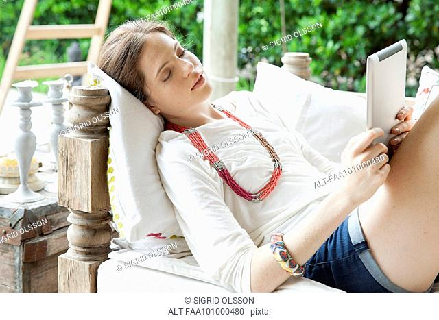 Young woman relaxing with digital tablet