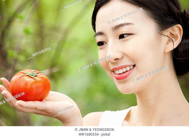 a woman holding a tomato in the nature