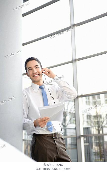 Smiling business man in office, headset