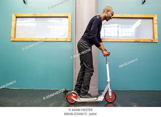 African American man riding scooter indoors