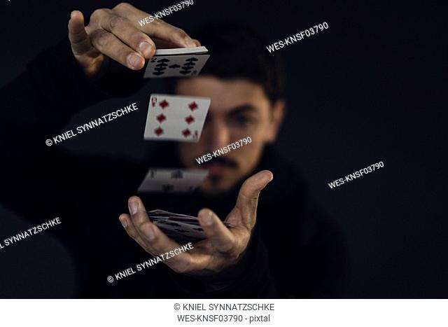 Magician conjuring with playing cards, close-up