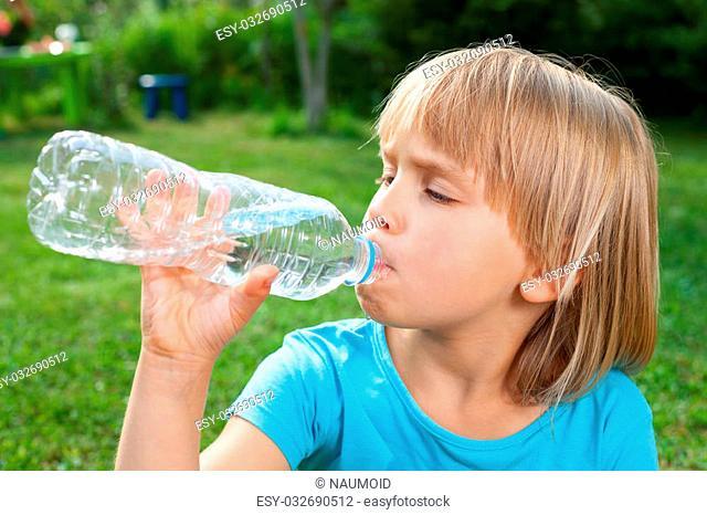 Cute little girl drinking water in a summer garden