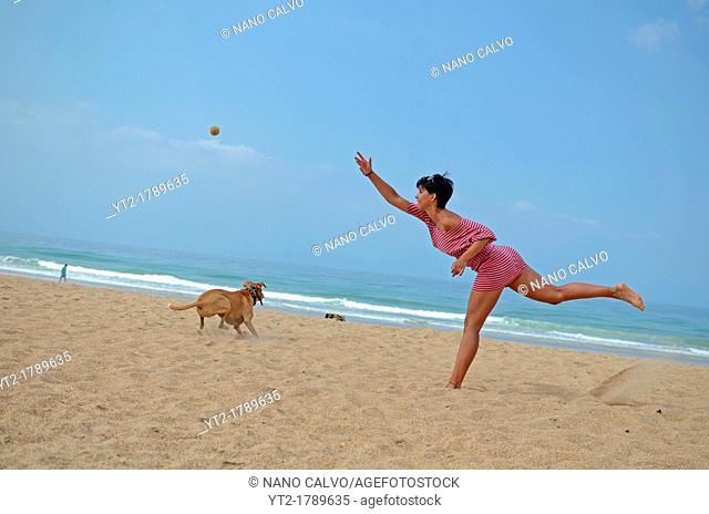 Young woman plays with dog on the beach
