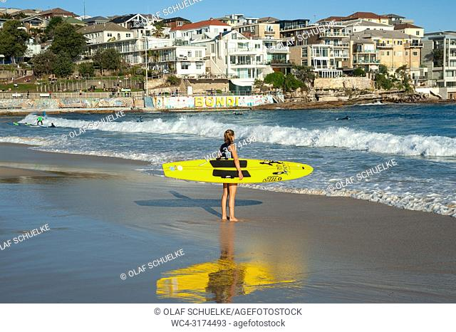 21. 09. 2018, Sydney, New South Wales, Australia - A young female surfer is seen holding her surfboard as she gazes at the open ocean at Bondi Beach