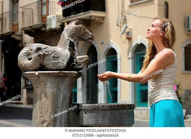Woman in the Horse drinking fountain outside Cathedral of St Nicola, Taormina, Sicily, Italy