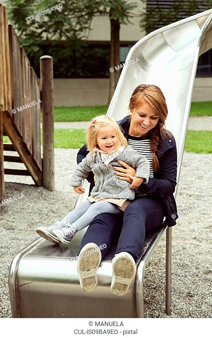 Mother and toddler daughter on playground slide