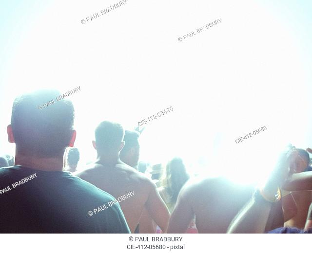Silhouette of fans facing illuminated stage