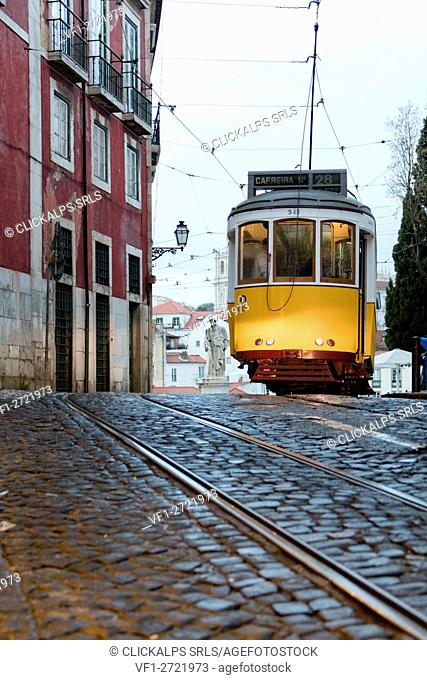 Yellow tram number 28 passes in Alfama district characterized by a typical architecture on a rainy day Lisbon Portugal Europe