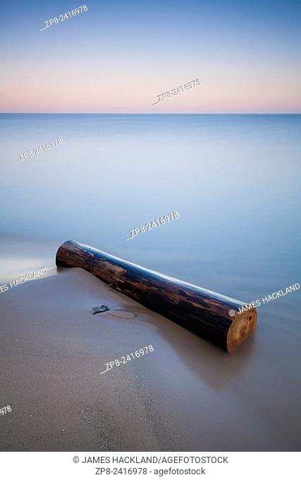 A long exposure creates a soft feel and mood to this image of a log washed ashore on a beach. Pinery Provincial Park, Ontario, Canada